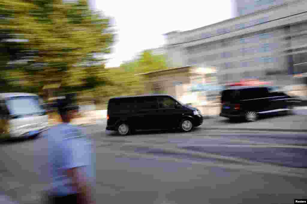 A minivan (C) believed to be carrying disgraced Chinese politician Bo Xilai arrives at the Jinan Intermediate People's Court ahead of the fifth day of Bo's trial in Jinan, Shandong province, August 26, 2013.