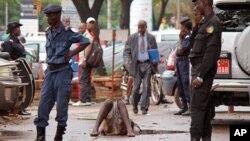 Cảnh sát bảo vệ khu vực nơi một người đàn ông bị nghi nhiễm Ebola nằm trên một vũng nước ở thành phố Conakry, Guinea.