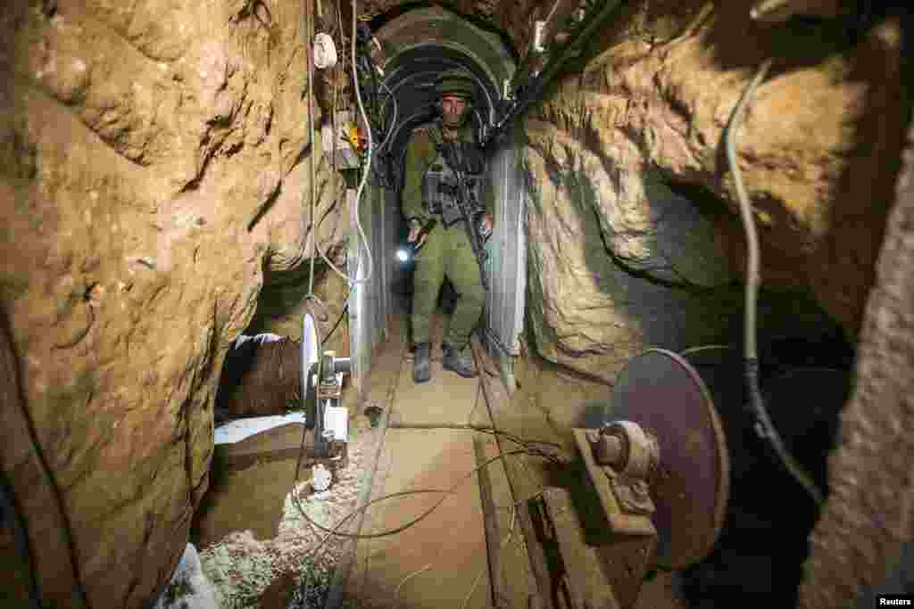 An Israeli army officer gives explanations to journalists during an army organized tour in a tunnel said to be used by Palestinian militants for cross-border attacks, July 25, 2014.
