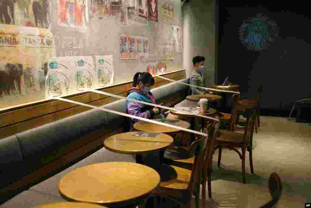 Tables and chairs are taped for the social distancing law enforcement to help curb the spread of the coronavirus at a Starbucks coffee shop in Hong Kong.
