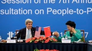 U.S. Secretary of State John Kerry, left, holds the hand of Chinese Vice Premier Liu Yandong after delivering a speech for the plenary session of the 7th annual U.S.-China High-Level Consultation on People-to-People Exchange.