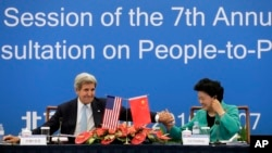 U.S. Secretary of State John Kerry, left, holds the hand of Chinese Vice Premier Liu Yandong after delivering a speech for the plenary session of the 7th annual U.S.-China High-Level Consultation on People-to-People Exchange at the National Museum in Beijing, June 7, 2016.