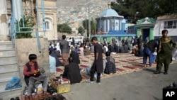 Varias personas se preparan para las oraciones del Eid al-Fitr, la festividad religiosa que marca el fin del Ramadán, afuera de una mezquita en Kabul.