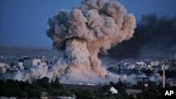 20일 터키 접경 마을 수루크에서 바라본 시리아 코바니에서 미군 주도 연합군의 공습으로 연기가 피어오르고 있다.