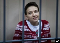 FILE - Ukrainian jailed military officer Nadezhda Savchenko sits in a cage at a court room in Moscow, Russia, March 4, 2015.