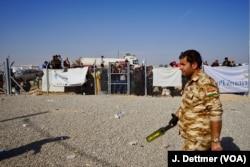 A Kurdish policeman patrols the entrance to the Khasir camp and displaced civilians sure waiting to enter the camp at Khasir.