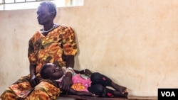 After crossing Nimule border, a woman and her child wait for a medical check up at Elegu reception center. (N. Jidovanu/VOA)