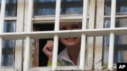 Mantan Perdana Menteri Ukraina Yulia Tymoshenko terlihat tersenyum dari balik teralis penjara di Kiev, Ukraina (Foto: dok). Tymoshenko tidak bersedia menghentikan aksi mogok makannya, sebagai bagian dari protes atas pelanggaran dalam pemilu parlemen di negara itu.