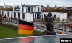 FILE - A German national flag flutters in front of the Chancellery in Berlin. The 2013 revelation that the U.S. National Security Agency had tapped German Chancellor Angela Merkel's mobile phone came from WikiLeaks.