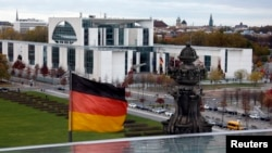 FILE - A German national flag flutters in front of the Chancellery in Berlin.