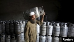 FILE - A worker carries a cylinder of Liquified Petroleum Gas at a gas distribution center in Peshawar, Pakistan April 29, 2015.