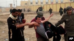 Protesters carry an injured man during clashes in Fallujah, 40 miles (65 kilometers) west of Baghdad, Iraq, January 25, 2013.