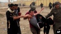 Một người bị thương trong cuộc xô xát được những người biểu tình mang đi. Cuộc biểu tình diễn ra ở Fallujah cách thủ đô Baghdad 65 km về hướng tây, 25/1/13