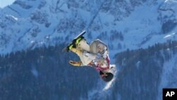 United States' Sage Kotsenburg takes jump during men's snowboard slopestyle final, Rosa Khutor Extreme Park, 2014 Winter Olympics, Sochi, Feb. 8, 2014.
