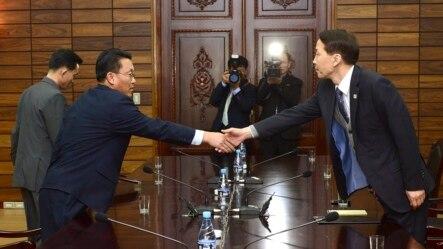韩国首席谈判代表金基雄(右)星期四在板门店朝鲜一侧与朝鲜首席谈判代表握手。(2015年11月26日 韩国统一部提供照片)