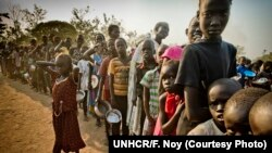 FILE - South Sudanese refugees wait in line to get food at Dzaipi transit camp in northern Uganda.