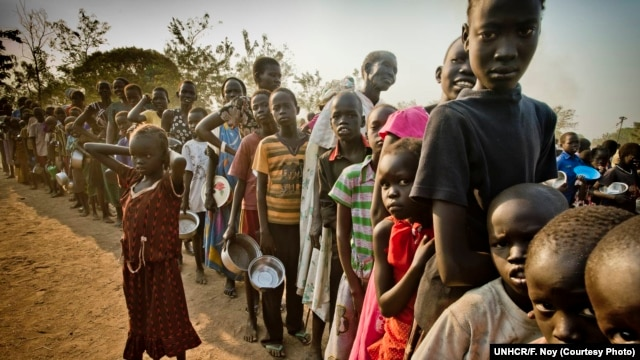 FILE - South Sudanese refugees wait in line to get food at Dzaipi transit camp in northern Uganda.