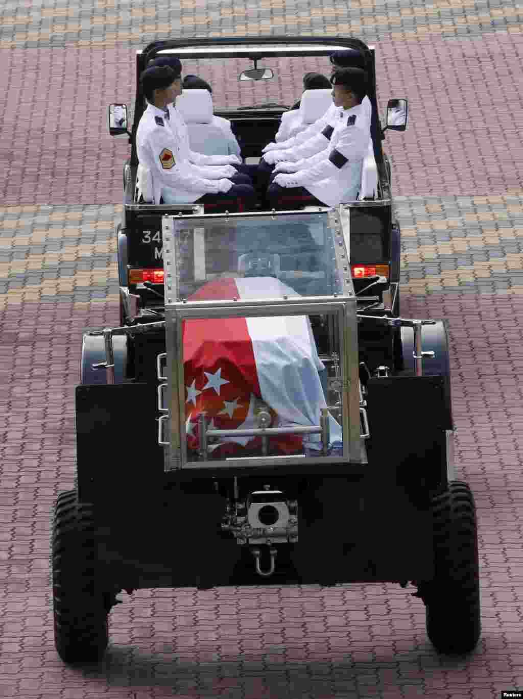 Kendaraan terbuka yang membawa jenazah perdana menteri pertama Singapura tiba di Gedung Parlemen tempat ia akan disemayamkan sampai Sabtu di Singapura (25/3).