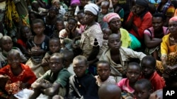 FILE - Refugees who fled Burundi's violence and political tension wait to board a ship freighted by the UN, at Kagunga on Lake Tanganyika, Tanzania, May 23, 2015.