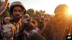 지난해 9월 요르단 람다의 난민촌에 도착한 시리아 난민들이 요르단 군인들로부터 식량을 받고 있다.