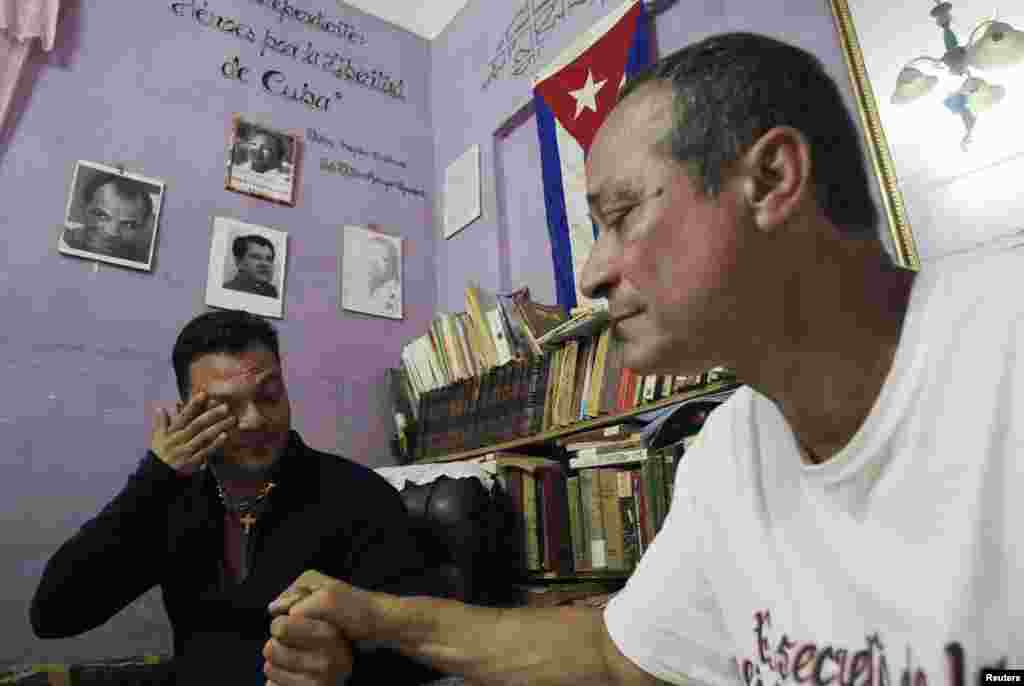 "Reinier Figueredo (left) reacts while holding his father Angel's hand at their home. Angel Figueredo and his wife Haydee Gallardo (not pictured), members of the ""Ladies in White"" dissident group, were detained last year after shouting anti-government slogans at a rally, in Havana, Cuba, Jan. 8, 2015."
