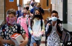FILE - Wearing masks to prevent the spread of COVID19, elementary school students walk to classes to begin their school day in Godley, Texas, Wednesday, Aug. 5, 2020. (AP Photo/LM Otero)