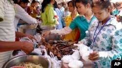 FILE - Cambodian Garment workers buy some cheap food for their lunch in front of the factory in downtown of Phnom Penh, Cambodia, March 10, 2011.