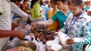 Cambodian Garment workers buy some cheap food for their lunch in front of the factory in downtown of Phnom Penh, Cambodia, Thursday, March 10, 2011. The workers are spent lest than USD $0.25 per daily meals in among of the monthly celeries of USD $61, sai