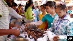 Công nhân Campuchia mua thực phẩm giá rẻ cho bữa trưa phía trước nhà máy ở trung tâm thành phố Phnom Penh.