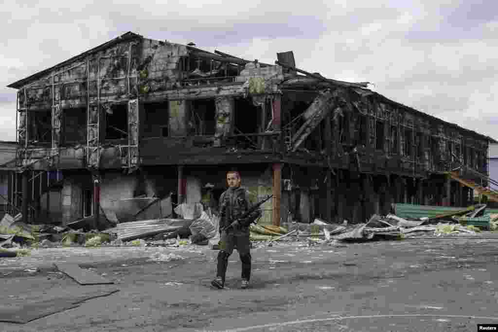 A pro-Russian rebel walks in front of a factory destroyed during recent shelling, in the town of Nizhnaya Krinka, eastern Ukraine.