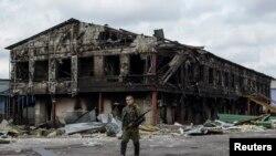 Phiến quân thân Nga canh gác phía trước một nhà máy bị phá hủy trong vụ pháo kích tại thị trấn Nizhnaya Krinka, miền đông Ukraine, ngày 23/9/2014.