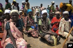 FILE - Women sit in line on the ground waiting to receive food aid in Padeah, South Sudan, March 1, 2017.