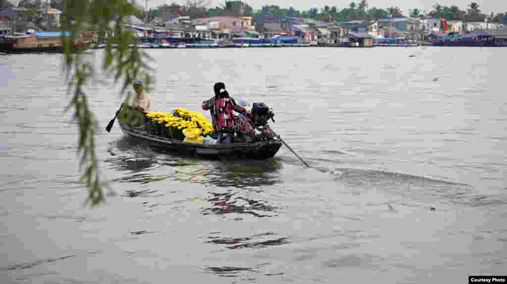 Người dân dùng thuyền gỗ qua sông ở bến Ninh Kiều, Cần Thơ , ngày 8 tháng 2 năm 2013 (Ảnh của Dungvo/Việt Nam/Độc giả VOA)