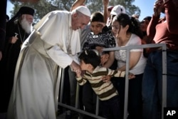 FILE - A child kisses the hand of Pope Francis during a visit at the Moria refugee camp on the island of Lesbos, Greece, April 16, 2016.