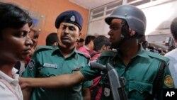 孟加拉国警察在达卡两人遇刺身亡的建筑物里试图控制旁观的人群。 (2016年4月25日)