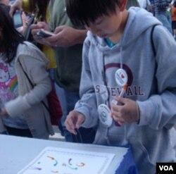 Brian Manivong membuat lukisan dengan belatung di gerai Maggot Monet di pameran sains dan teknik nasional Washington DC