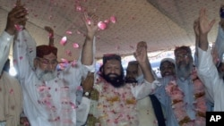 Malik Ishaq, center, a leader of the banned Sunni Muslim group Lashkar-e-Jhangvi, and his colleagues raise hands to response their supporters July 15, 2011