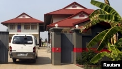 FILE - A van enters a residence that temporarily housed asylum seekers coming from a remote South Pacific detention center, in Phnom Penh, Cambodia. Gen. Tan Sovichea, head of the refugee office in Cambodia's Interior Ministry, said the Iranian couple departed for Iran on February 12.