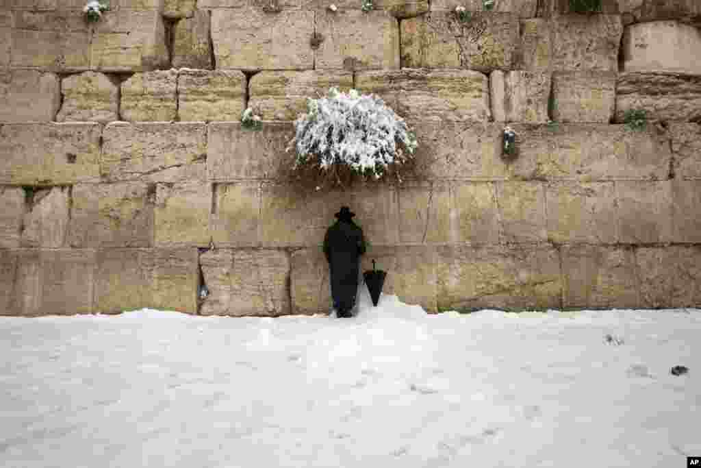 An ultra-Orthodox Jewish man prays at the Western Wall, the holiest site where Jews can pray in Jerusalem's old city. A heavy winter storm hit parts of the Middle East on Friday, with snow forcing roads leading in and out of Jerusalem to close.