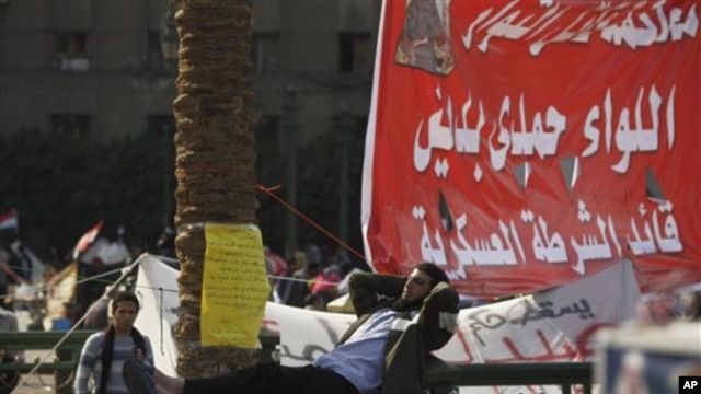 "An Egyptian man rests on a fence in Tahrir Square in Cairo, Egypt, Sunday, Nov. 27, 2011. Egypt's activists are staging a massive protest in Cairo's Tahrir Square to press demands for the country's military rulers to step down. The Sunday rally, dubbed ""L"