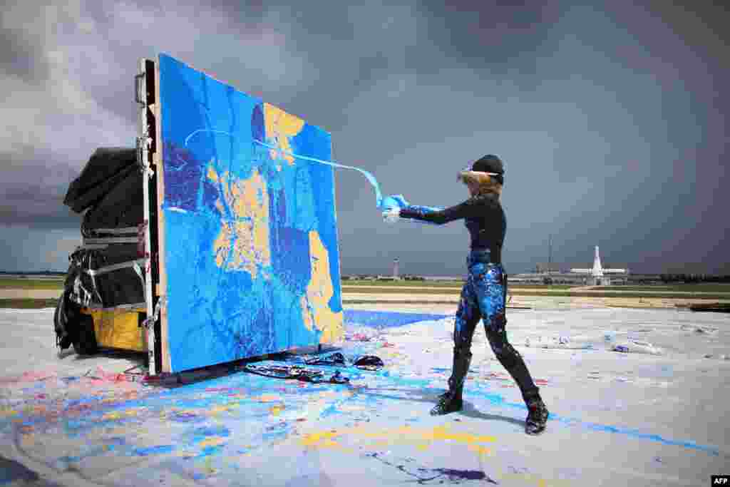Artist Princess Tarinan von Anhalt throws paint into the flow of air coming from the engine of Flexjet's Learjet 40 XR engine to create a painting on a canvas at Signature Flight Support in West Palm Beach, Florida, USA, Apr. 30, 2013.