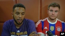 In this image made from TV, Anthony Sadler, a senior at Sacramento State University, left, sits with Alek Skarlatos, U.S. National Guardsman from Roseburg, Oregon, who both helped overpower high-speed train attacker, talk to the media early Saturday Aug. 22