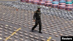 A Colombian police officer walks near packs of confiscated marijuana and cocaine in Cali April 15, 2013. The police confiscated 5.3 tons (10,600 lbs) of marijuana and 877kg (1,933 lbs) of cocaine in the departments of Valle and Cauca during Operation Repu