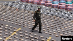 A Colombian police officer walks near packs of confiscated marijuana and cocaine.