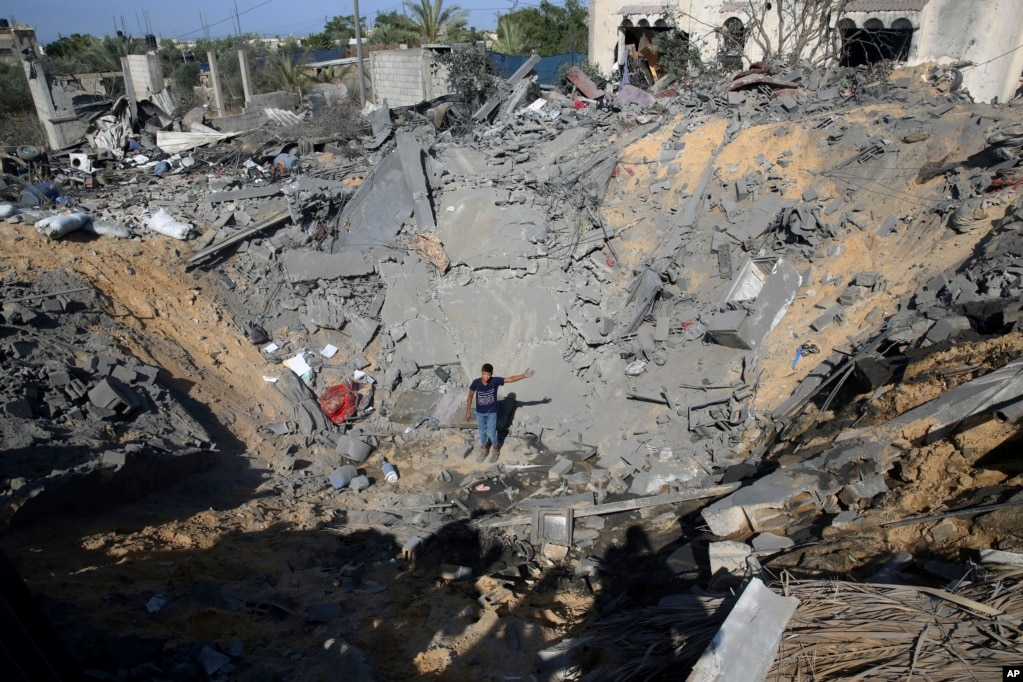 A Palestinian youth stands in the hole of a destroyed house following overnight Israeli missile strikes, in Al-Qarara, east of Khan Younis, southern Gaza Strip.