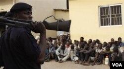 Polisi berjaga-jaga sementara massa menunggu di luar pengadilan di Kaduna, Nigeria (20/4).