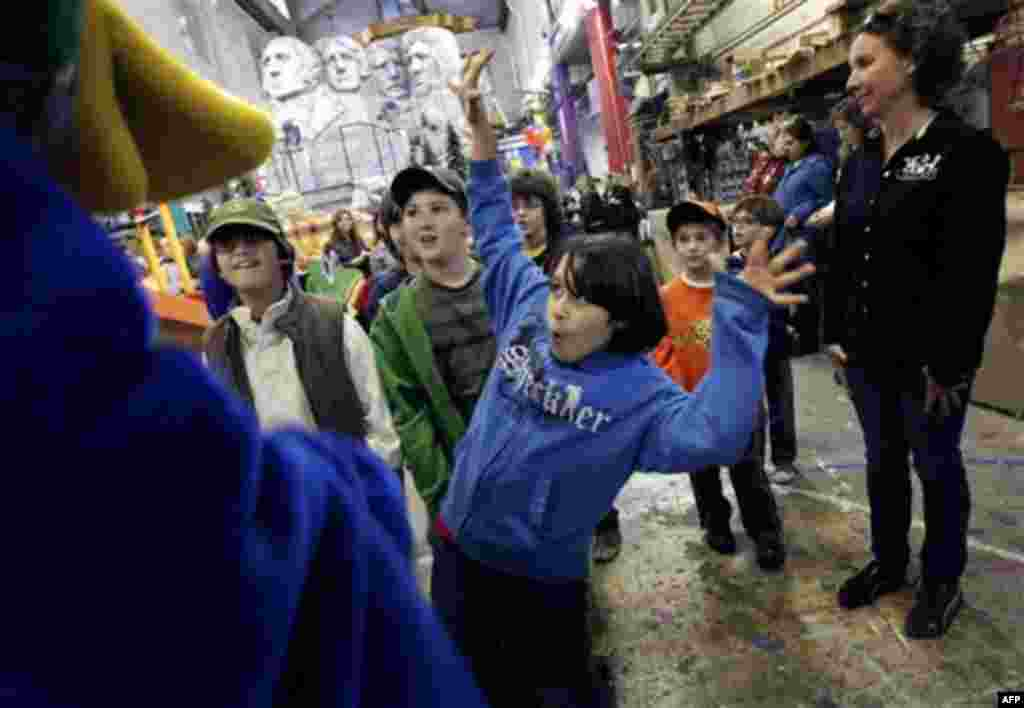 Brian Ray Torres, 11, greets Lewis the Duck during a tour of the Macy's Parade Studio in Hoboken, N.J., Tuesday, Nov. 16, 2010. (AP Photo/Seth Wenig)