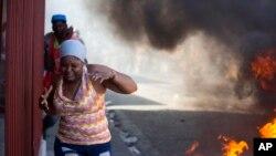 Una mujer pasa corriendo junto a barricadas de neumáticos ardiendo durante una nueva protesta para exigir cómo se gastaron los fondos de Petro Caribe en Haití.