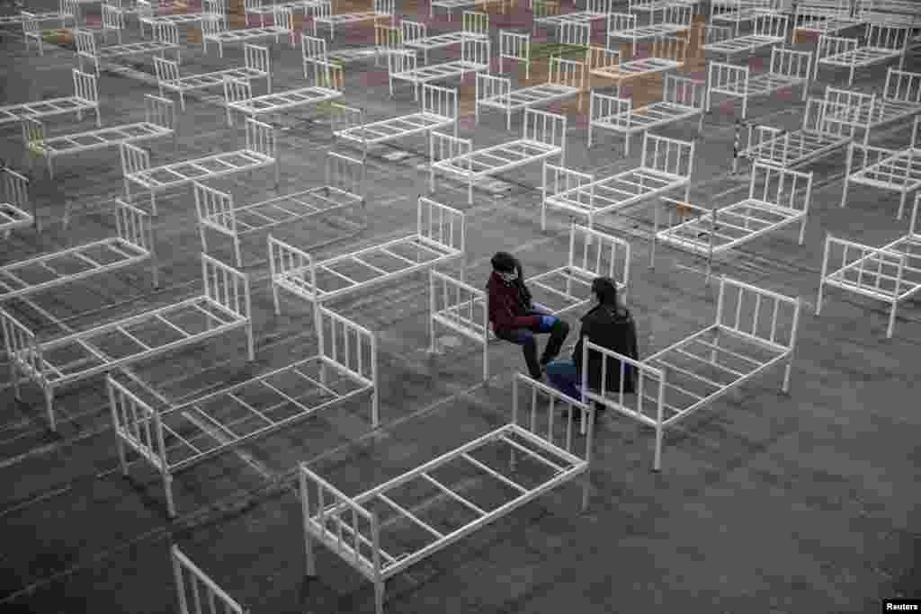 Volunteers take a break as they set up beds inside the Novi Sad Fair to accommodate people who suffer mild symptoms of coronavirus disease in Novi Sad, Serbia.