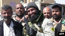Ayyub Faleh al-Rubaie (center), known as Abu Azrael, poses with Shiite fighters at the Speicher military base, near the northern Iraqi city of Tikrit, on March 14, 2015.